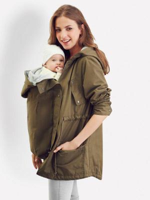 junge Mutter trägt ihr Baby vorn im Umstandsparka