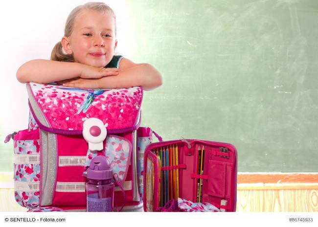 Mädchen ist stoltz auf ihren neuen pinken Schulranzen und seine Ausstattung