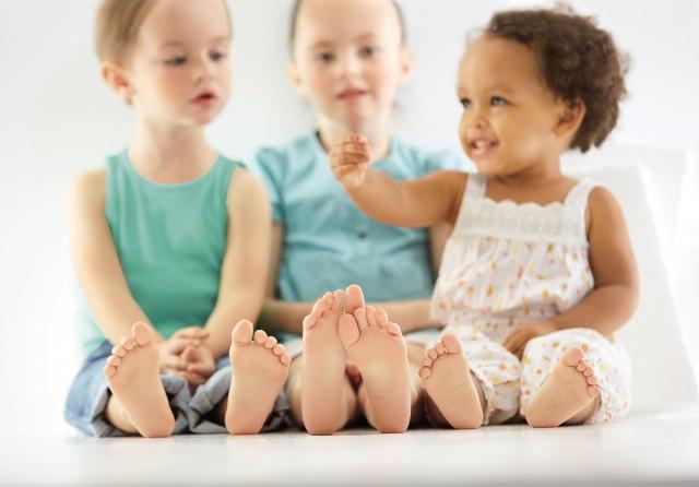 kleine Kinder sitzen barfuß