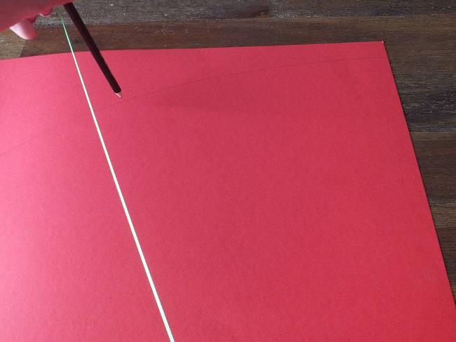 mit einem Bleistift wird ein Bogen auf rotes Tonpapier gezeichnet