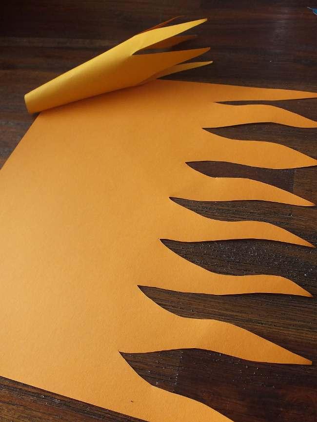 aus orangefarbenem Tonpapier wird eine Flammenleiste ausgeschnitten