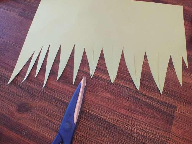 grünes Papier wird zackig ausgeschnitten, um Gras anzudeuten