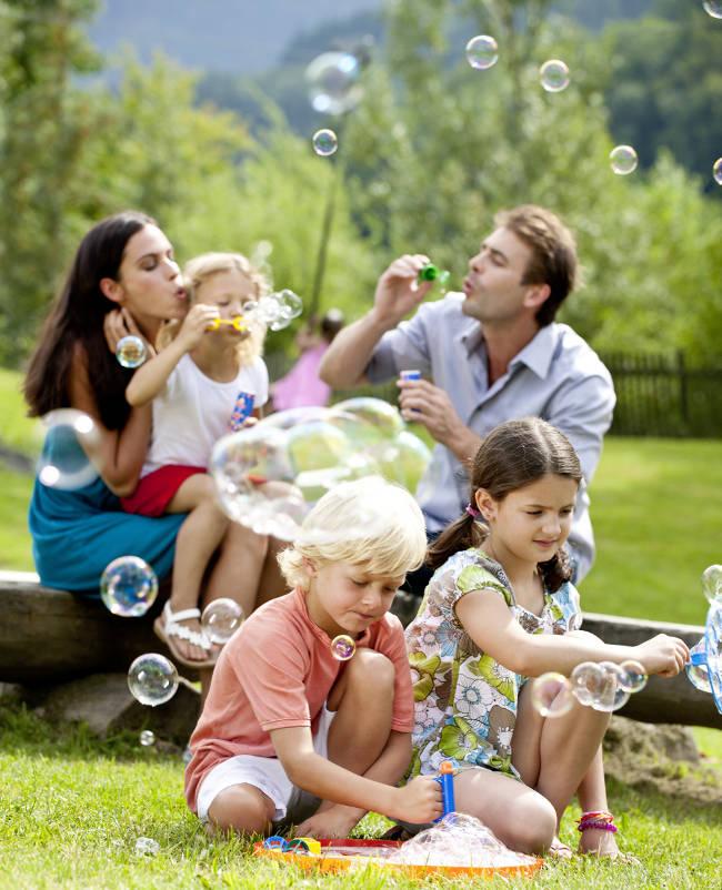 Familie macht zusammen Seifenblase auf einer Sommerwiese