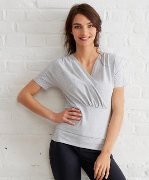 eine junge Schwangere im Sportoutfit